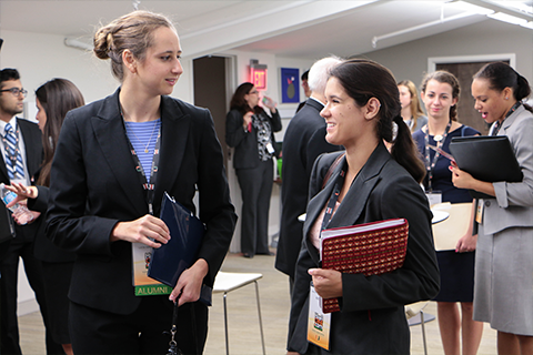 Two students conversing at networking event