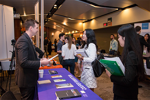 two students speaking to employer at event