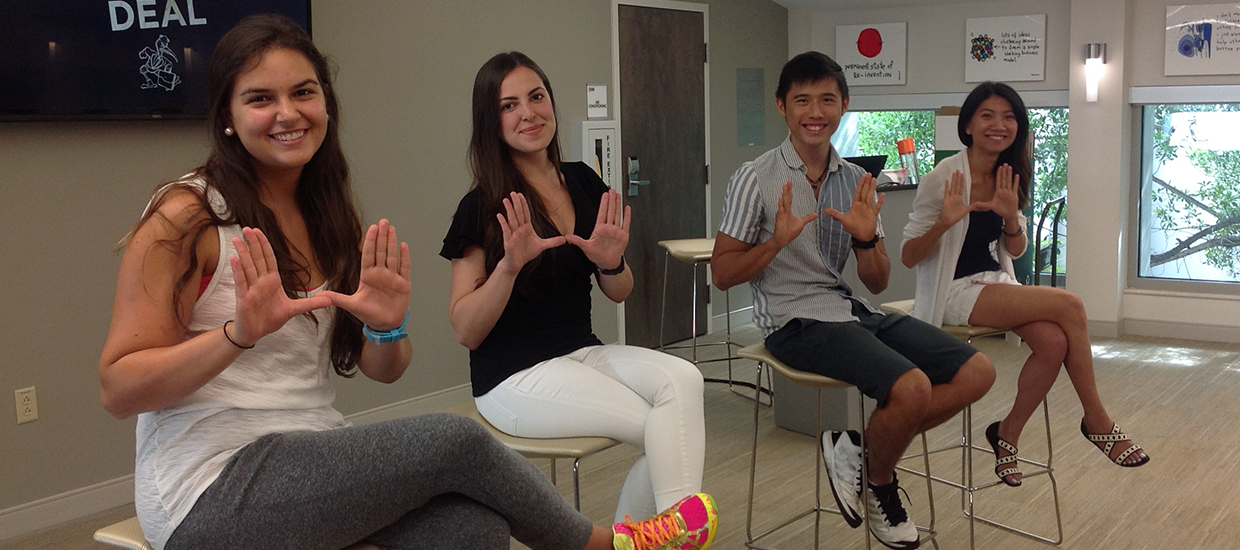 Four international students holding up the U symbol